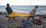 The body of a refugee child is carried along a beach on the Greek island of Lesbos on November 1, 2015.  It was covered with a plastic raincoat by Spanish lifeguards until it could be picked up by local authorities.  The body appeared to be that of an Afghan boy of about 8 years of age. Thousands of refugees have died this year attempting to cross the Aegean from Turkey to Greece. Fleeing violence in Syria, Iraq, Afghanistan and elsewhere, most are on their way toward western Europe.