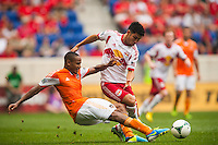 Ricardo Clark (13) of the Houston Dynamo tackles the ball away from Kosuke Kimura (27) of the New York Red Bulls. The New York Red Bulls defeated the Houston Dynamo 2-0 during a Major League Soccer (MLS) match at Red Bull Arena in Harrison, NJ, on June 30, 2013.