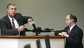 Charles Colman, Bureau of Alcohol, Tobacco, and Firearms (ATF) fingerprint expert, holds the Bushmaster rifle used in the sniper shootings as defense attorney Peter Greenspun, right, listens during testimony in the trial of sniper suspect John Allen Muhammad, in courtroom 10 at the Virginia Beach Circuit Court in Virginia Beach, Virginia on November 5, 2003.<br /> Credit: Dave Ellis - Pool via CNP