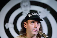 Chief organizer Emmanuel Goldstein stands in front of the official logo as he addresses the audience during the closing events of the 6th edition of HOPE, an annual hackers' convention, July 23rd 2006, New York City, USA.
