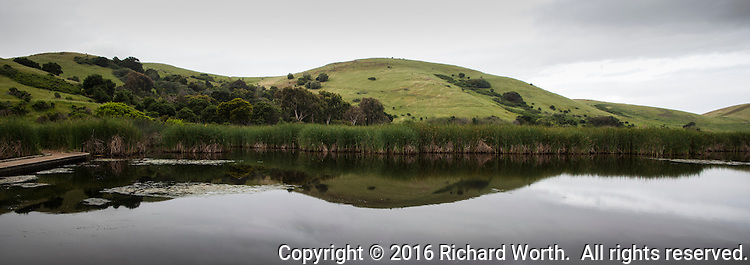 Green rolling hills and gray clouds reflect on still marsh waters in an  8.5X3 perspective panoramic.