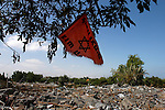 "An orange-colored anti-Disengagement flag (which reads: ""Gush Katif forever"") hangs over the rubble of ruined houses, at the settlement of Netzer Hazani, in the Israeli settlement bloc of Gush Katif, Gaza Strip, two weeks after Israel evacuated some 8000 settlers from the conflicted strip."