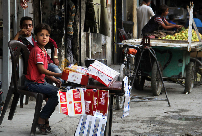 A Syrian boy sells cigarettes in a market in a rebel-controlled area in the northern Syrian city of Aleppo, on August 31, 2015. Photo by Ameer al-Halbi