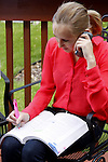 A young woman studying outside while on the phone