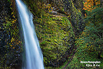 A fine art photograph of a waterfall and fall colors in a gorge in Oregon state.