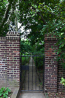 Wrought iron garden gate with brick pillars.