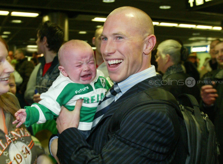Member of the Irish rugby team Peter Stringer is greeted by Rugby fan Sean McHugh (4 months) from Donnycarney following their Triple Crown victory against England at Dublin Airport..19/3/2006.Photo: Gareth Chaney Collins