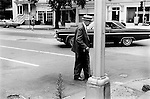 Princeton New Jersey USA 1969 An old man  crosses the road using a walking stick and  wearing a boater straw hat.