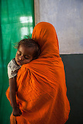 25 year old Dayawati and her 17 month son, Naresh Mukhiya wait to meet the Health post incharge at the local health centre in Hanuman Nagar in Saptari, Nepal. <br /> Naresh Mukhiya was first admitted on July 17, 2013 when he was 9 months old. MUAC - 109 mm, Weight - 5.5kg, and Height - 65 cm. He was discharged on Oct 1st, 2013. MUAC at the time of discharge - 123, Weight - 6.5 Kg, Height - 66cm. Total RUTF consumes - 148 sachets.Gain of weight - 2gm.day.