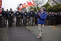 manifestation pour le travail, una manifestante con bandiera del partito comunista sfila davanti alla polizia schierata