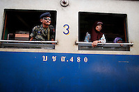 Muslim women look through the window of a train next to an armed man securing it before departing a station in the troubled Yala province in the southern Thailand February 28, 2011. Separatists are blamed for most of the attacks on Thailand's predominantly Muslim deep south, which often target Buddhists and Muslims associated with the Thai state, such as police, soldiers, government officials and teachers. No credible group has claimed responsibility for near daily drive-by shootings and bombings, which continue unabated, despite a massive counterinsurgency effort. Yala and Pattani are two of three Muslim-dominated provinces bordering Malaysia where more than 4,300 people, both Muslims and Buddhists, have been killed in a low-level insurgency since 2004.   REUTERS/Damir Sagolj (THAILAND)