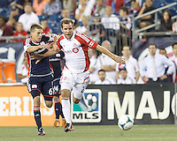 Toronto FC forward Jeremy Brockie (22) on the attack as New England Revolution midfielder Scott Caldwell (6) defends. In a Major League Soccer (MLS) match, Toronto FC (white/red) defeated the New England Revolution (blue), 1-0, at Gillette Stadium on August 4, 2013.