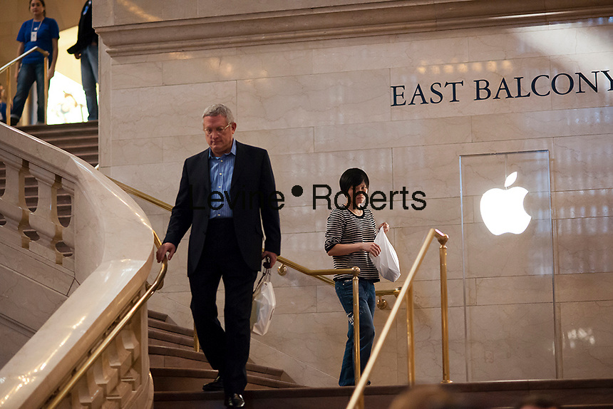 Customers leave the Apple store in Grand Central Terminal with their purchases on Friday, September 21, 2012.  The fifth generation of Apple's iPhone, the iPhone 5,  went on sale today bringing crowds and lines to Apple stores around the world. (© Richard B. Levine)