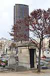 A tomb in Montparnasse Cemetery, Paris, with Montparnasse Tower behind