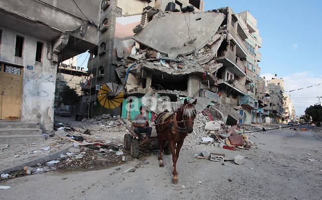 Palestinians walk past a building that was destroyed nearby their house following an Israeli air strike on July 19, 2014, in Gaza City. Israeli air strikes in the Gaza Strip killed 11 people early on July 19, medics said, on day 12 of a major operation against the Palestinian territory.. Photo by Ashraf Amra