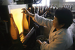 Before bottles of sake are capped, the sake must past one last test, as a worker uses an amber light to check if all sediment has been filtered out at a sake factory near Hachinohe, Japan. (Jim Bryant Photo).....