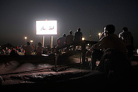 Locals gather under the glare of the new giant screens which line Khartoum's main transport route to and from the airport.