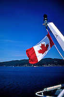 The Maple Leaf flag of Canada flying from the stern of a BC Ferry sailing to Victoria, BC.