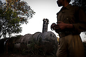 A police man points to the gas tank which leaked its contents into the atmosphere at the site of the deserted Union Carbide factory on November 28, 2009 in Bhopal, India. Twenty-five years after an explosion causing a mass gas leak, in the Union Carbide factory in Bhopal, killed at least eight thousand people, toxic material from the 'biggest industrial disaster in history' continues to affect Bhopalis. A new generation is growing up sick, disabled and struggling for justice. The effects of the disaster on the health of generations to come, both through genetics, transferred from gas victims to their children and through the ongoing severe contamination, caused by the Union Carbide factory, has only started to develop visible forms recently. Photograph: Sanjit Das