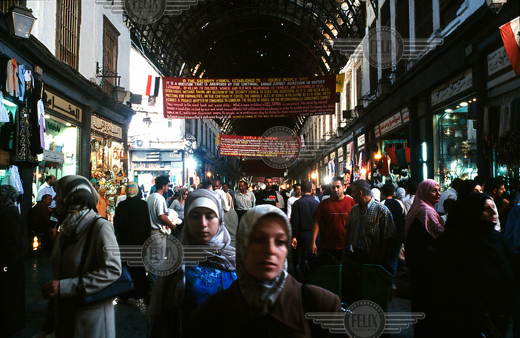 People walk beneath banners, supporting of Lebanon and Hezbollah, hanging in the main entrance to the Al-Hamidiyah Souq.