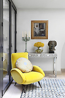 A vibrant architectural 60s chair in mustard velvet brings in more style, combined with the hague blue of the geometric carpet. A display of carefully chosen objects is arranged on a table behind.