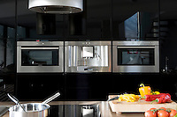 In the kitchen/living area a microwave and a pair of ovens are set into black high-gloss parapan cupboards ranged along the wall behind the large Quartz stone kitchen island