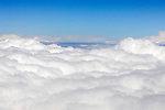 Stock photo of White clouds over blue sky close-up aerial view from a plane flying above clouds Horizontal background
