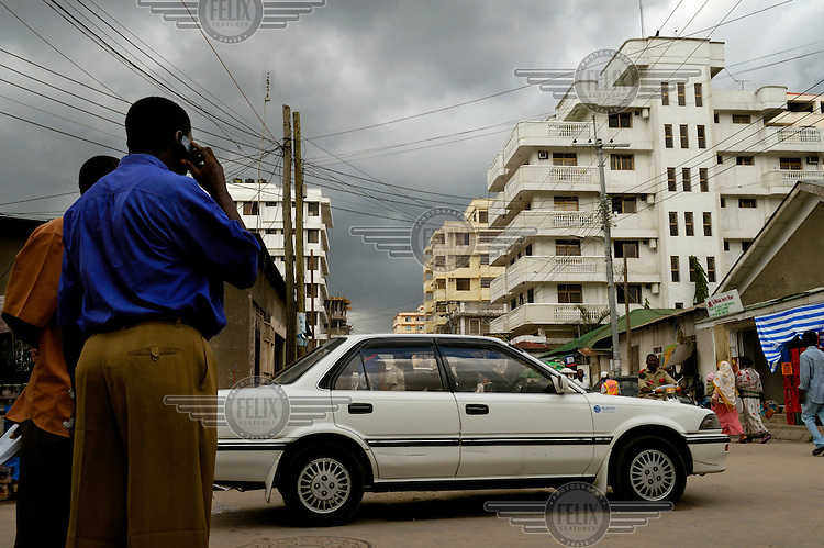 Man using his mobile telephone on the corner of a street lined with apartment buildings in the Kariakoo district, as a car drives past...