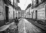 A man pushes a cart down the cobbled streets of Sorata, Bolivia.