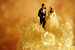 Traditional marriage ceremony with African American black couple (figurines) on wedding cake with sunset light.