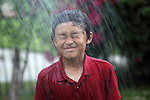Young boy enjoys water spray shower - EXCLUSIVELY AVAILABLE HERE