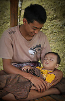 A young Balinese father provides comfort to his sleeping baby in a shady shelter away from  the hot afternoon sun.