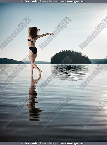 Young woman in swimsuit dancing in the sun on the water in beautiful morning sunrise nature scenery. Muskoka, Ontario, Canada.