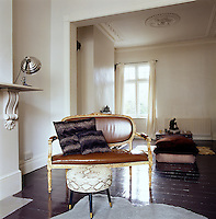 An under-furnished classical Victorian double drawing room has a stained and polished wood floor