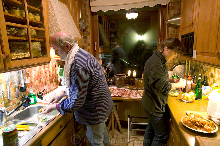 (MODEL RELEASED IMAGE). Working together in the kitchen to prepare dinner for guests, Jörg and Susanne prepare rouladen, a traditional German entrée consisting of pickles, mustard, and Westphalian bacon, rolled up in a thick slice of beef, cooked, and served in rich brown gravy. This is a favorite meal of the Melander family. (Supporting image from the project Hungry Planet: What the World Eats.) The Melander family of Bargteheide, Germany, is one of the thirty families featured, with a weeks' worth of food, in the book Hungry Planet: What the World Eats.