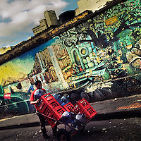 A Colombian shop assistant transports crates of soft drinks in front of the wall, covered in a mural artwork, in the center of Bogotá, Colombia, 19 February 2016. A social environment full of violence and inequality (making the street art an authentic form of expression), with a surprisingly liberal approach to the street art from Bogotá authorities, have given a rise to one of the most exciting and unique urban art scenes in the world. While it's technically not illegal to scrawl on Bogotá's walls, artists may take their time and paint in broad daylight, covering the walls of Bogotá not only in territory tags and primitive scrawls but in large, elaborate artworks with strong artistic style and concept. Bogotá has become an open-air gallery of contemporary street art.