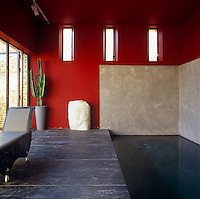 Natural slate floors and deep red walls lend a stark serenity to the indoor swimming pool