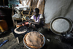 A displaced woman cooks bread over a fire in her makeshift hut in Agok, a town in the contested Abyei region where tens of thousands of people fled in 2011 after an attack by soldiers and militias from the northern Republic of Sudan on most parts of Abyei. Although the 2005 Comprehensive Peace Agreement called for residents of Abyei--which sits on the border between Sudan and South Sudan--to hold a referendum on whether they wanted to align with the north or the newly independent South Sudan, the government in Khartoum and northern-backed Misseriya nomads, excluded from voting as they only live part of the year in Abyei, blocked the vote and attacked the majority Dinka Ngok population. The African Union has proposed a new peace plan, including a referendum to be held in October 2013, but it has been rejected by the Misseriya and Khartoum. The Catholic parish of Abyei, with support from Caritas South Sudan and other international church partners, has maintained its pastoral presence among the displaced and assisted them with food, shelter, and other relief supplies.