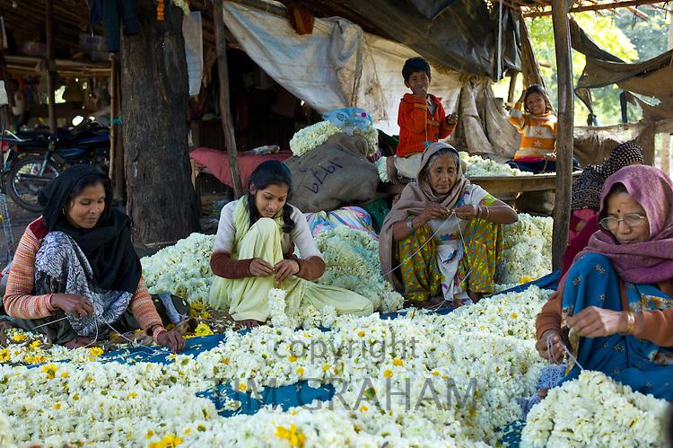 Indian women and children at work stringing garlands at Mehrauli Flower Market, New Delhi, India
