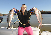 NWA Democrat-Gazette/FLIP PUTTHOFF<br /> Erica Crafford shows two striped bass she caught Dec. 4, 2015 using brood minnows in the Hickory Creek area of Beaver Lake. Fishing is good through the winter on the south end of Beaver Lake with live bait or lures. Anglers may catch a variety of fish, including stripers, hybrid stripers or white bass.