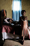 A young girl stands next to her mothers bed on August 17, 2000 Izingolweni, a rural village in Southern Natal in South Africa. The mother is dying of an Aids related disease in her home. The girls will be taken care of by grandparents as no other relatives can care for the child. South Africa has one of the highest infection rates of HIV/Aids in the world. (Photo by: Per-Anders Pettersson)