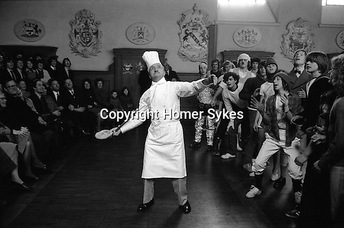 Westminster School annual Shrove Tuesday Pancake Greaze Westminster, London, England 1976. Head Chef Sam Sellars. tosses the pancake. Boys scramble for a piece of the pancake.<br /> <br /> It can be safely assumed that the Pancake Greaze at Westminster School has a long history although the first reference to it is in the works of the philosopher of Utilitarianism, Jeremy Bentham, a scholar there from 1755 to 1760. He wrote: 'The Higher School was divided from the Lower by a bar, and it was one of our pastimes to get the cook to throw a pancake over it.' Regrettably, he gives no further detail.<br /> In the nineteenth century, as in Bentham's time, the whole school of over two hundred pupils took part. Disapproval by the headmaster in 1883 led to a change whereby only one boy from each form was allowed to try for the pancake.<br /> Traditionally the pancake is brought into school at 11 a.m. preceded by the college beadle with his mace, and followed by the dean's verger, the dean and the headmaster. On a signal from the latter the cook attempts to toss the pancake over the pancake bar to a line of waiting boys. A Greaze ensues and the boy with the most cake is declared the winner. In the past he received a golden guinea from the dean, but for some time now this has always been returned after the ceremony and cash is given in its place. Until 1860 the guinea was not presented if the pancake was torn or touched the ground. Also if the cook failed to toss the pancake over the pancake bar he was 'booked'. For the last decade it has become the custom to wear fancy dress, which might be anything<br /> from a specially-hired gorilla's outfit to the colours of a Chelsea football supporter.<br /> At the end of the ceremony, as is customary at all official functions, the dean 'begs a play', which the headmaster grants. This is a half-holiday for all the school, and nowadays is normally fitted into half-term break.