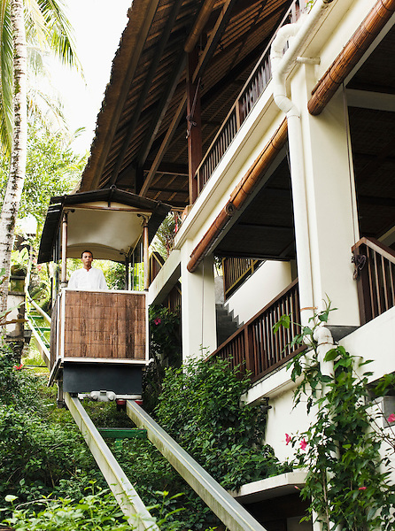 Balinese man rides the funicular (or tram) at Ubud Hanging Gardens, Bali, Indonesia. The funicular runs from the main lobby to Diatas Pohon Cafe.