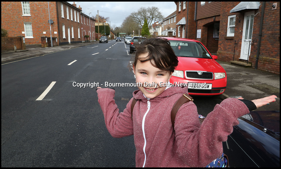 BNPS.co.uk (01202 558833)<br /> Pic: CorinMesser/BNPS<br /> <br /> ***Please use full byline***<br /> <br /> Wimborne resident Bella Harvey, (10).<br /> <br /> At first glance it would appear the worker who painted these wonky white lines might have had one too many in the pub.<br /> <br /> Rather than the normal straight white lines running down the centre of the road, drivers are facing weird winding markings that wiggle down the carriageway.<br /> <br /> They have been baffling motorists since they appeared on a street in Wimborne, Dorset.<br /> <br /> But road chiefs insist they are deliberate, forming part of a bizarre calming measure aimed at slowing down traffic in a notorious rat run by forcing drivers to follow a curving course.