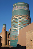 Low angle view of Kalta Minor, 1855, and detail of the Matniyaz Divan-begi Madrasah (left), 1871, Khiva, Uzbekistan, pictured on July 6, 2010, at dawn. The Kalta Minor or Short Minaret was commissioned by Mohammed Amin Khan in 1852 to stand 70 m. high, but was abandoned when he died in 1855, and remains only 26 m. high. Commissioned by Muhammad Niyaz the rectangular, Madrasah has a traditional main facade, its high portal, decorated with majolica, having a central pentahedral niche and corner guldastas which are geometrically patterned in blue, white and green, with green brick domes. Khiva, ancient and remote, is the most intact Silk Road city. Ichan Kala, its old town, was the first site in Uzbekistan to become a World Heritage Site(1991). Picture by Manuel Cohen.