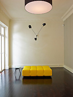 A bright yellow ottoman creates a focus of colour in the living room beneath a Serge Mouille wall light