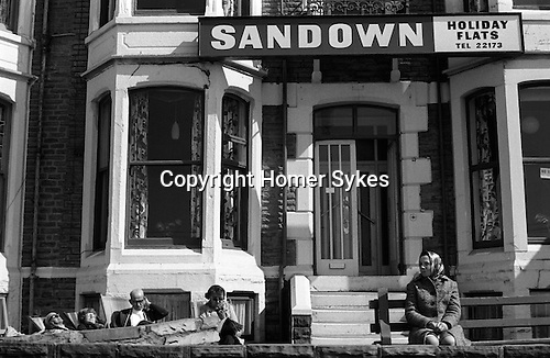 """PEOPLE ON HOLIDAY IN BLACKPOOL, ENJOY THE SUNSHINE SITTING OUTSIDE THEIR HOLIDAY FLATS OVER LOOKING THE """"GOLDEN MILE """" 1970S UK"""
