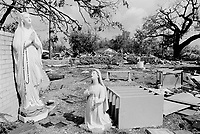 USA. Mississippi. Biloxi. Aftermath of hurricane Katrina. In a garden, behind the church, two statues of the Virgin Mary, the Queen of Peace. One praying and another on her knees. Most houses were  destroyed by the storm, the tidal surge (water wave) and the floods. The area is now empty and all its inhabitants have left away. The people could no longer and ever live again in the houses. The entire area needs to be bulldozed before any new construction can be built. Household waste. Destruction of the urban american way of life.© 2005 Didier Ruef