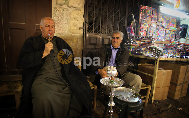 Palestinian men smoke hookah at a cafe in Jerusalem's Old City on February 12, 2014. Minister of Holy Places for the PA Mahmoud al-Habbash told Israel's Channel 10 network that the PA wants control of all the areas in Jerusalem that were won by Israel during the 1967 Six-Day War, including the Western Wall. Photo by Saeed Qaq