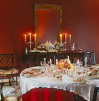 The remains of a good dinner are in evidence on the round table in this intimate red candlelit dining room
